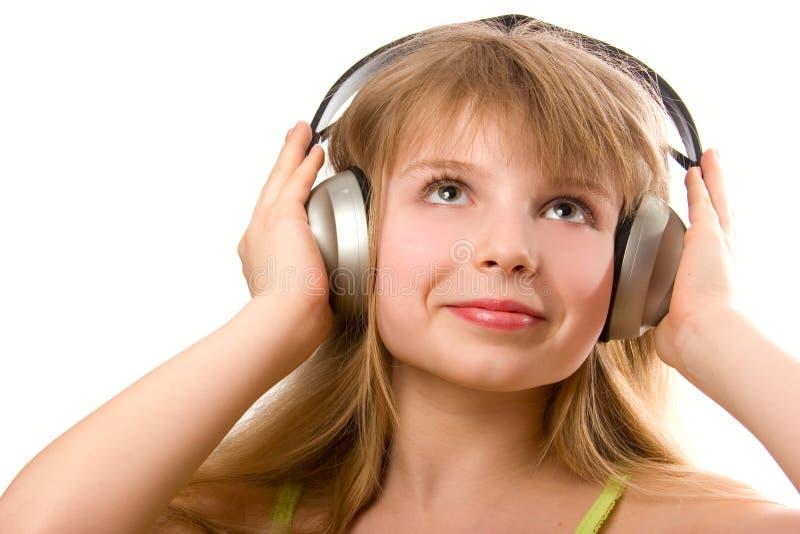 Belle fille heureuse avec des écouteurs photographie stock libre de droits