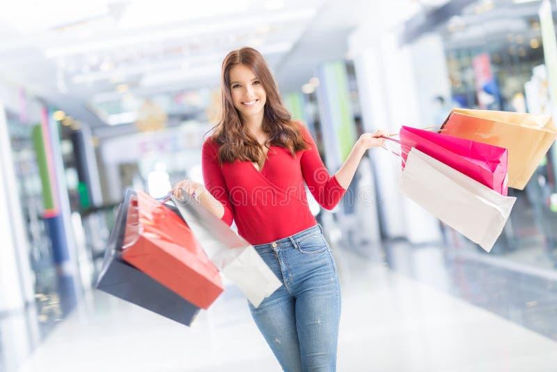 Belle fille heureuse avec la carte de crédit et paniers dans le shopp photos libres de droits