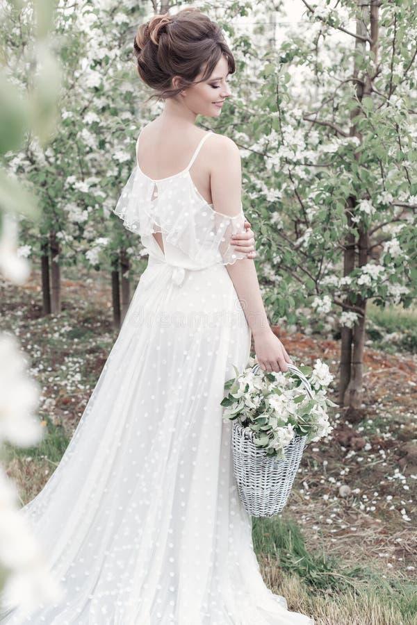 Belle fille heureuse douce douce dans une robe beige de boudoir avec des fleurs dans une exploitation de panier, photo traitant d images stock