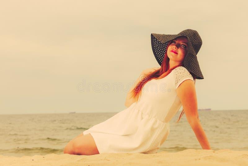 Belle fille heureuse redhaired dans le chapeau noir sur la plage photos stock