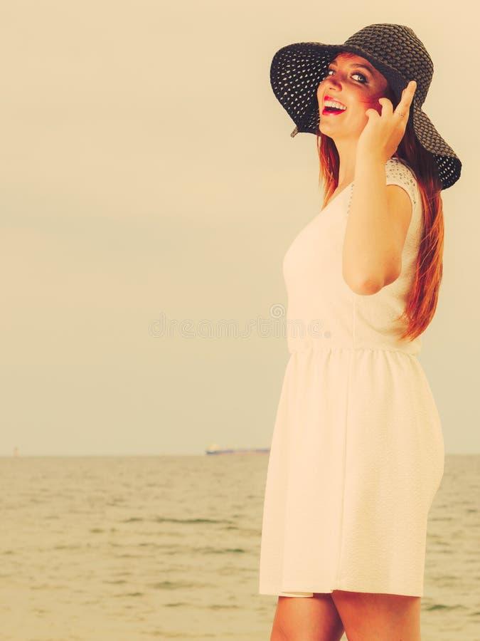 Belle fille heureuse redhaired dans le chapeau noir sur la plage photo stock