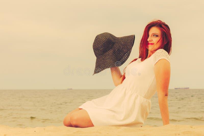 Belle fille heureuse redhaired dans le chapeau noir sur la plage image libre de droits