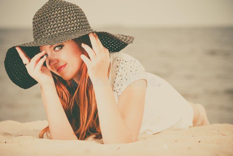 Belle fille heureuse redhaired dans le chapeau noir sur la plage images stock