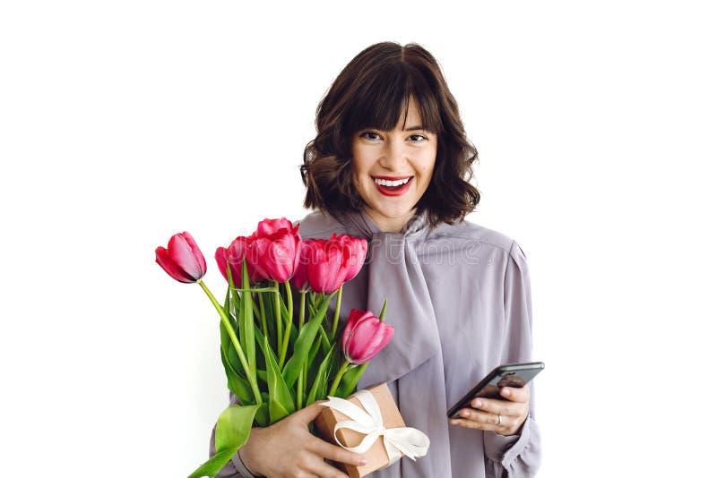 Belle fille heureuse tenant les tulipes, le boîte-cadeau et le téléphone rouges sur le fond blanc à l'intérieur, l'espace pour le images stock