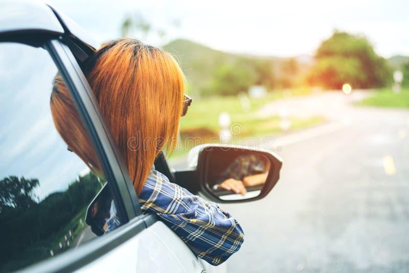 Belle fille heureuse voyageant dans une voiture de berline avec hayon arrière images libres de droits
