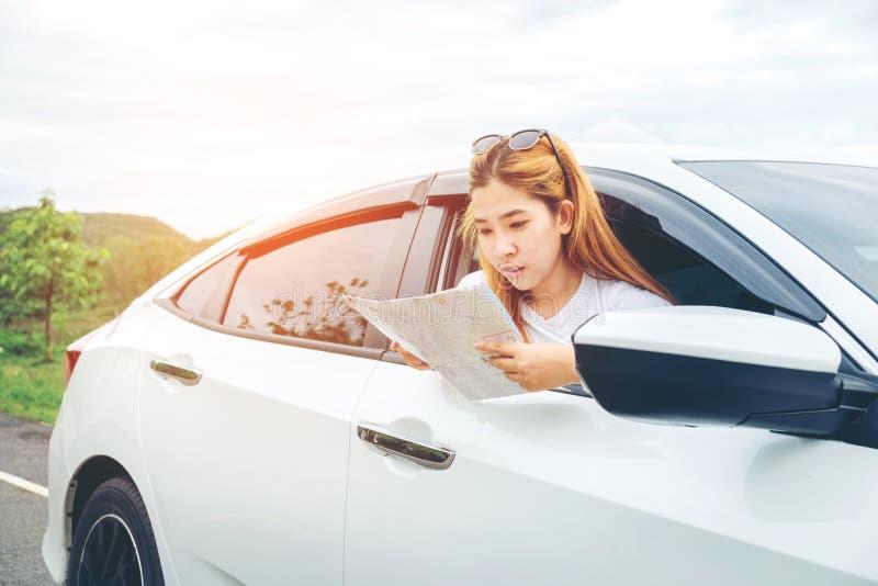 Belle fille heureuse voyageant dans une voiture de berline avec hayon arrière avec la carte image libre de droits