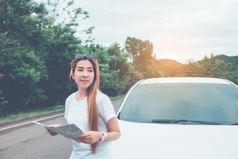 Belle fille heureuse voyageant dans une voiture de berline avec hayon arrière avec la carte photos stock