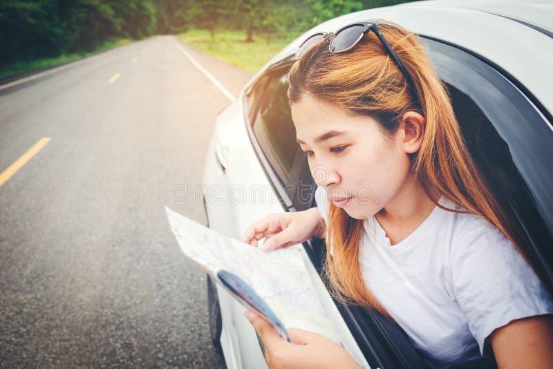 Belle fille heureuse voyageant dans une voiture de berline avec hayon arrière avec la carte images libres de droits