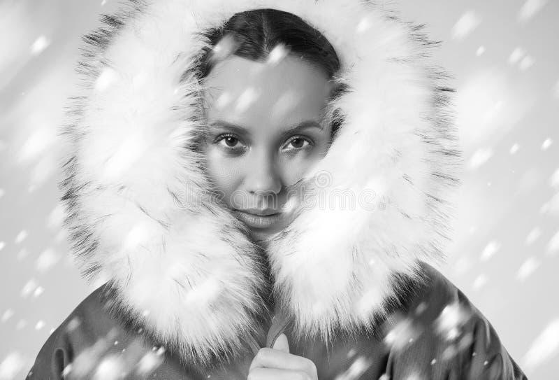 Belle fille hispanique avec du charme dans le manteau bleu avec la neige en baisse image stock