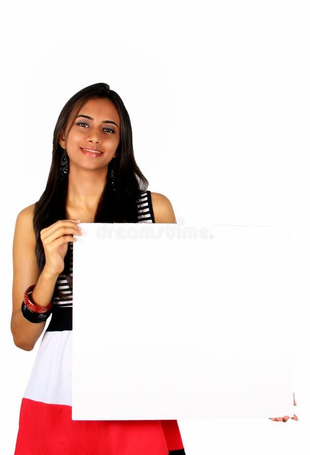 Belle fille indienne retenant un panneau blanc. image libre de droits
