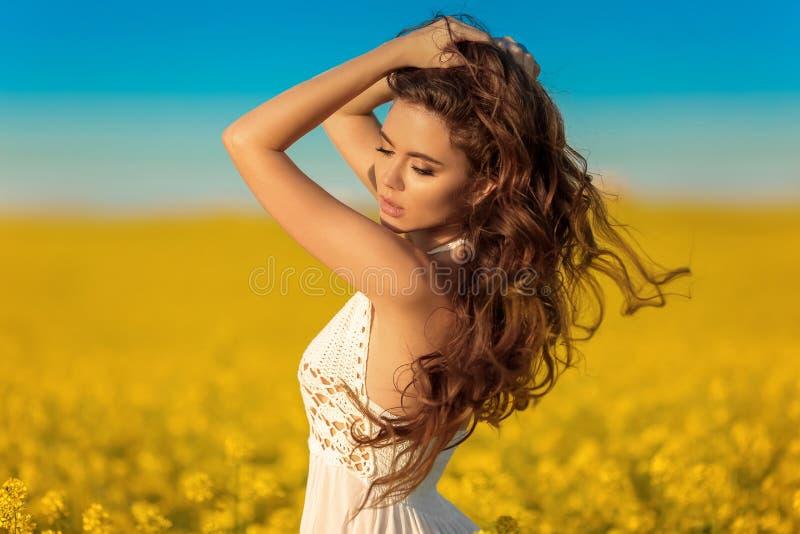 Belle fille insouciante avec de longs cheveux sains bouclés au-dessus de fond jaune de paysage de champ de viol Brune d'Attracive photographie stock