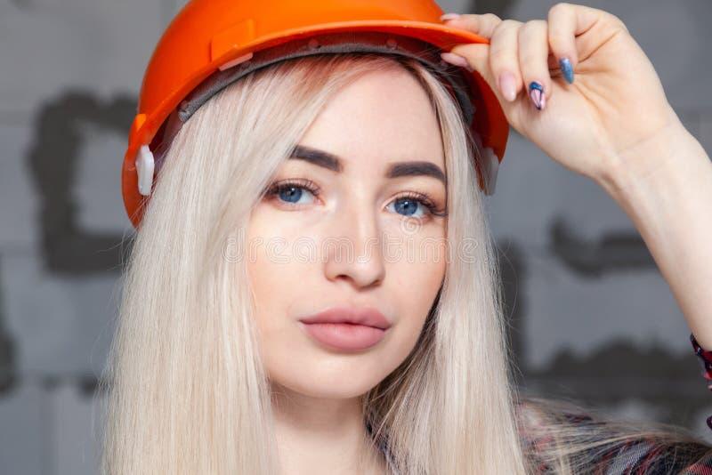 Belle fille la blonde d'agent de maîtrise de concepteur dans un casque orange de construction et des combinaisons de jeans Concep photographie stock libre de droits