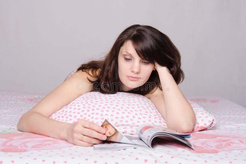 Belle fille lisant pensivement un magazine dans le lit photographie stock