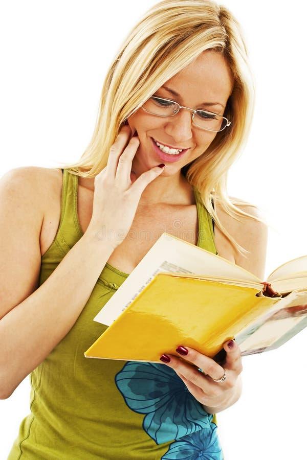 Belle fille lisant un livre et un sourire photos libres de droits