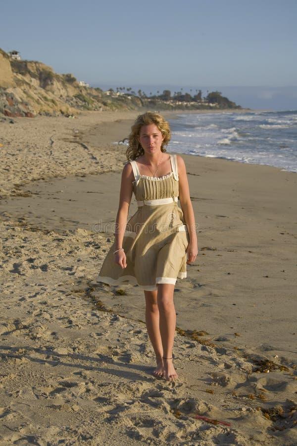 Belle fille marchant sur la plage dans la robe image stock