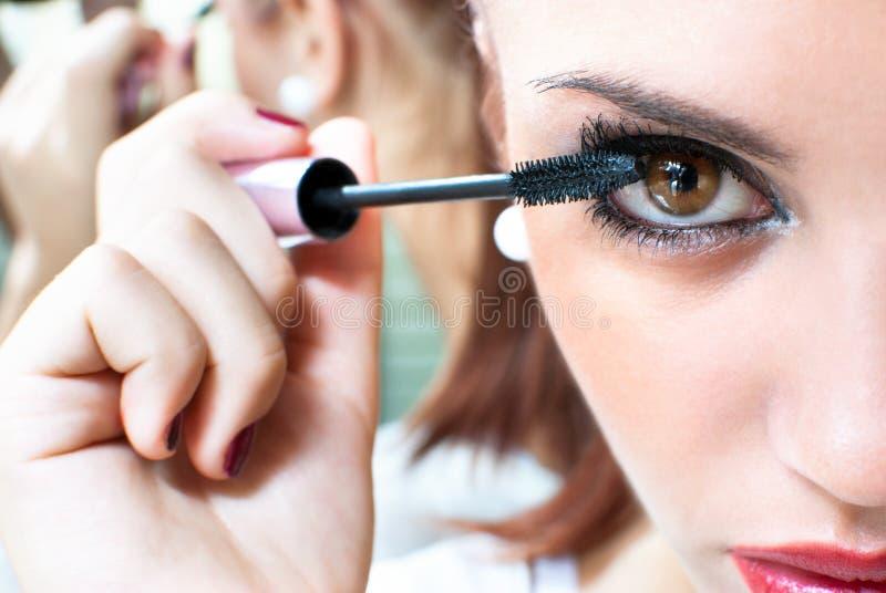 Belle fille mettant le maquillage sur ses yeux photo stock
