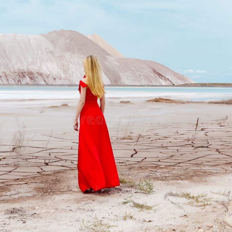 Belle fille mignonne sexy avec de longs cheveux blonds dans une longue robe de soirée rouge se tenant dans le désert près des mon photo stock