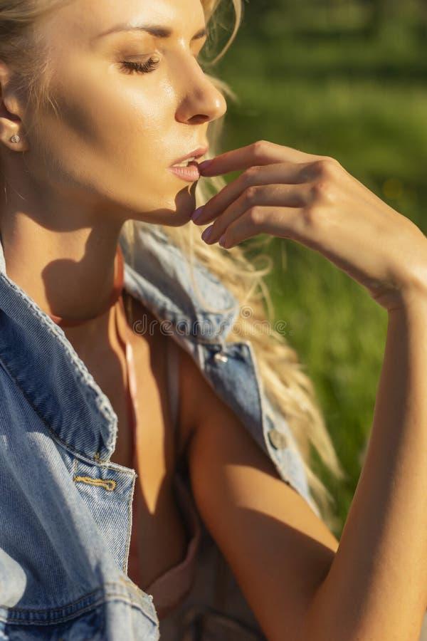 Belle fille mince blonde portant le jacke rose de lingerie et de jeans photographie stock
