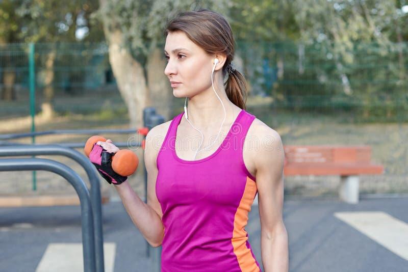 Belle fille mince et sportive dans des trains lumineux de vêtements de sport avec l'haltère pour le biceps au sportground extérie image libre de droits