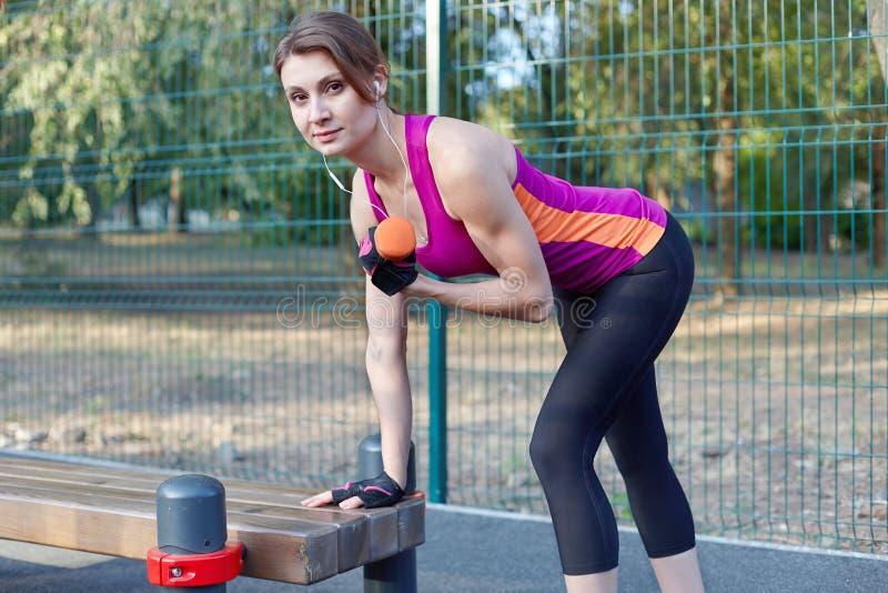 Belle fille mince souriant, dans des trains lumineux de vêtements de sport avec l'haltère pour le biceps au sportsground extérieu photos stock