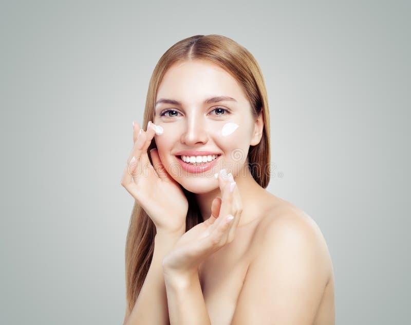 Belle fille modèle appliquant le traitement crème cosmétique sur son visage sur le blanc Verticale saine de femme photographie stock