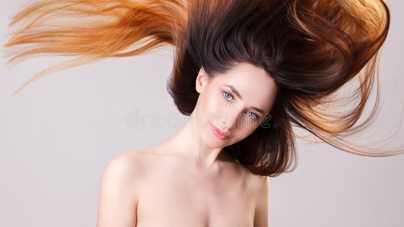 Belle fille modèle avec cheveux droits de vol d'ombre brillant de brun de longs Soin et produits capillaires images stock