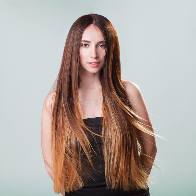Belle fille modèle avec cheveux droits de vol d'ombre brillant de brun de longs Soin et produits capillaires photographie stock