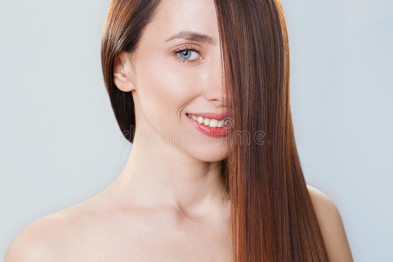 Belle fille modèle avec de longs cheveux droits bruns brillants Soin et produits capillaires image libre de droits