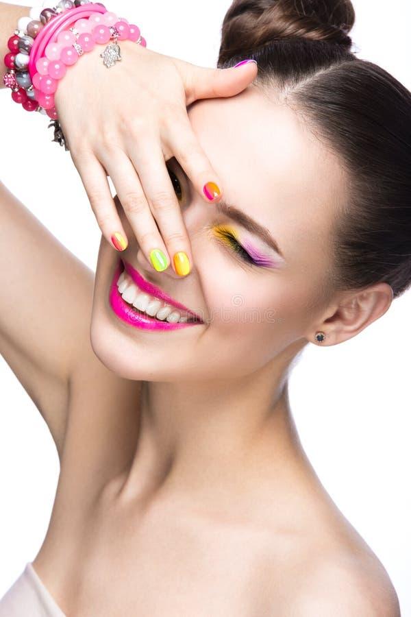 Belle fille modèle avec le maquillage coloré lumineux et vernis à ongles dans l'image d'été Visage de beauté Clous colorés par sh photo stock