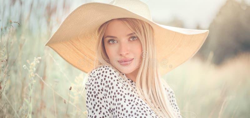Belle fille modèle posant sur un champ, appréciant l'extérieur de nature dans le chapeau de paille débordé large jeune femme de b photos stock
