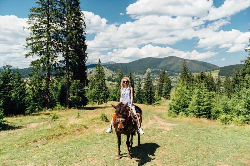Belle fille montant un cheval dans les montagnes images stock