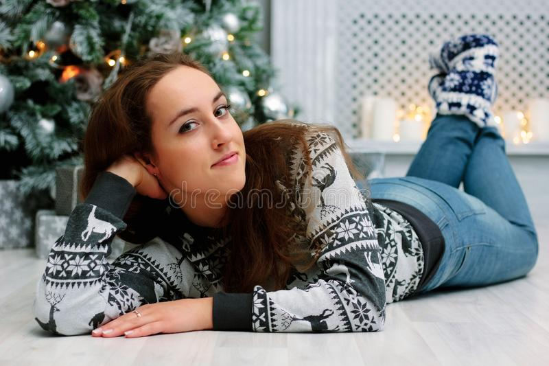 Belle fille pendant le Noël fixant sur le plancher près de l'arbre de Noël photos stock