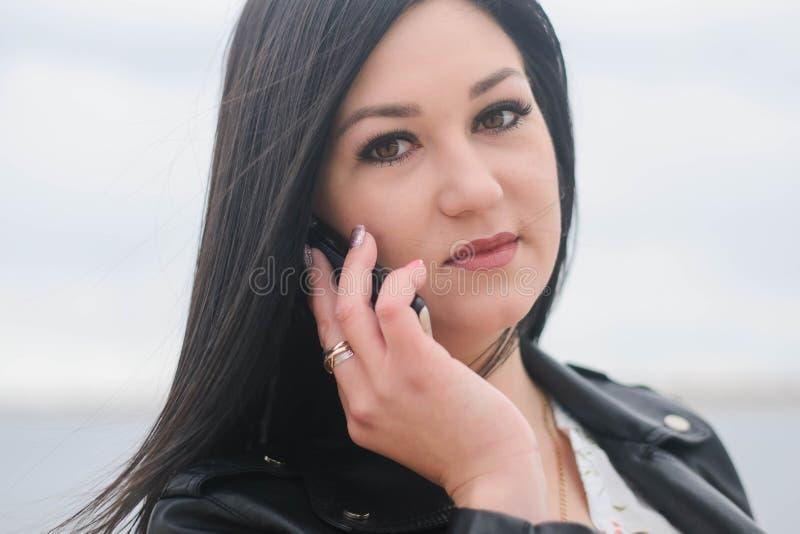 Belle fille posant contre le contexte de la rivière photo stock