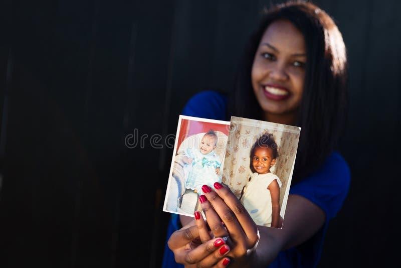 Belle fille posant tenant ses photos de bébé photographie stock