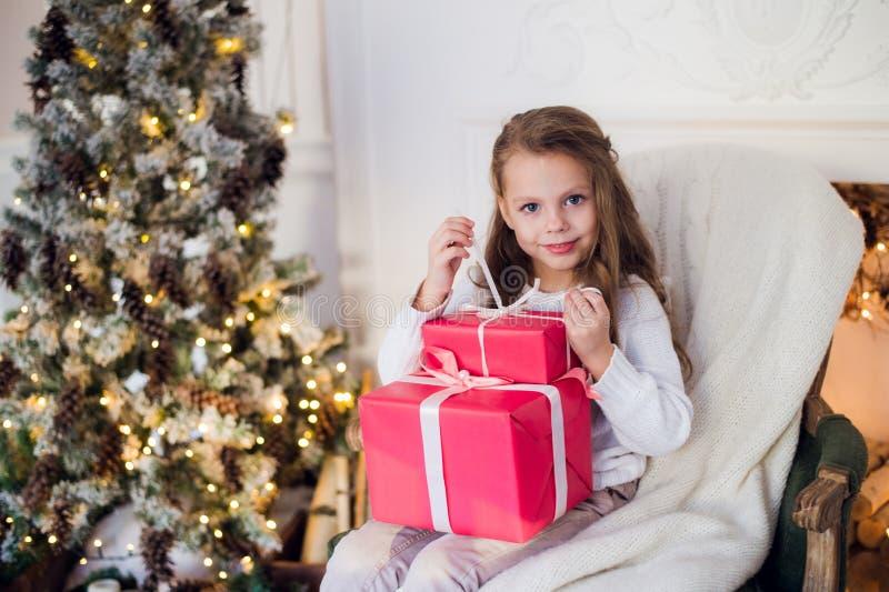 Belle fille près de l'arbre de Noël déballant des présents se reposant sur une chaise photos libres de droits