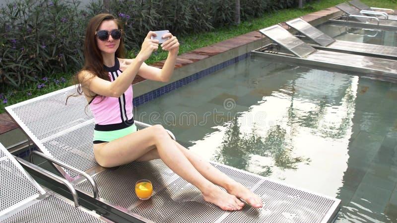 Belle fille prenant le selfie et riant de la piscine en villa de luxe photo libre de droits