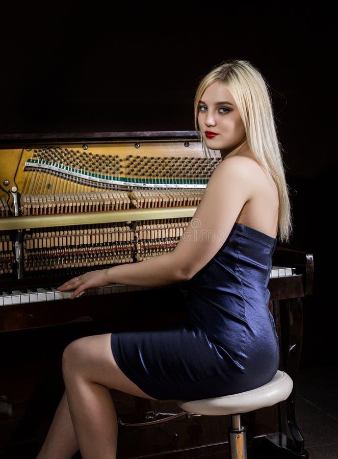 Belle fille réfléchie s'asseyant près du piano sur un fond foncé images libres de droits