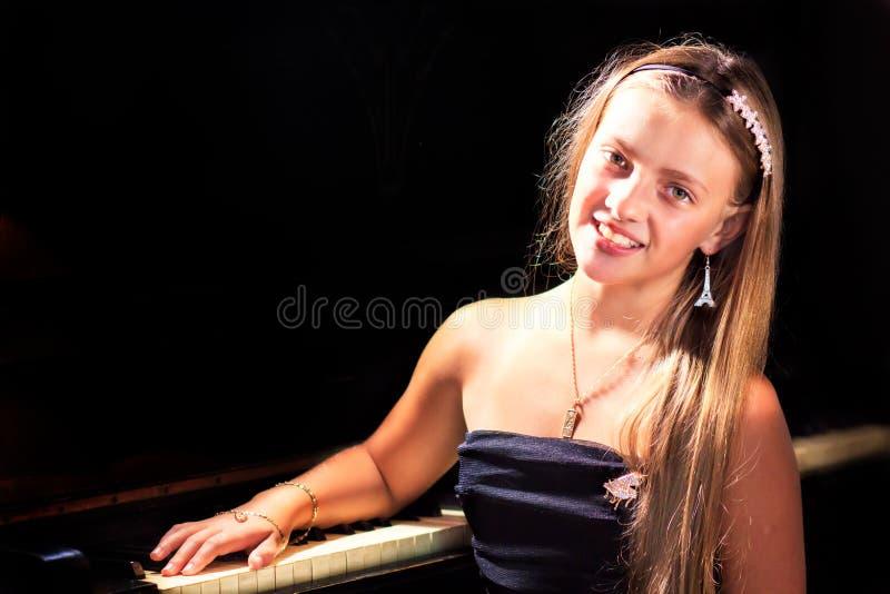 Belle fille réfléchie s'asseyant près du piano sur un fond foncé photographie stock
