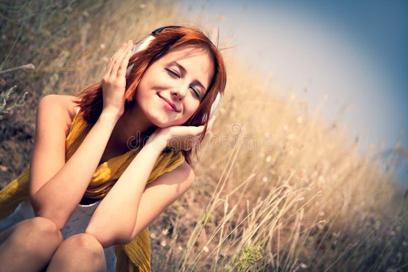 Belle fille red-haired à l'herbe avec des écouteurs photos libres de droits