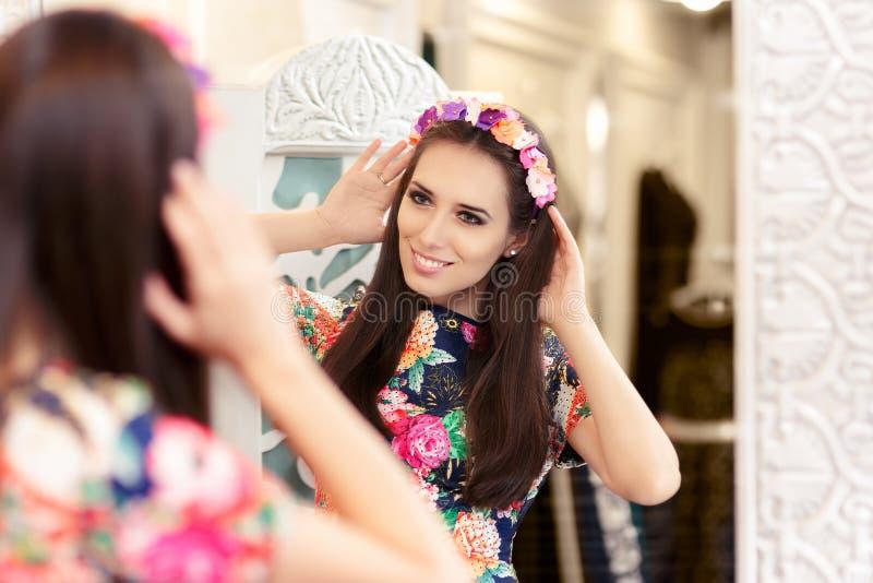 Belle fille regardant dans le miroir et essayant sur la robe florale photographie stock