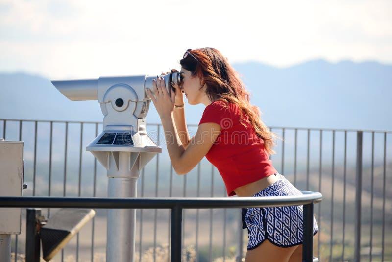 Belle fille regardant le paysage par la pièce de monnaie binoculaire photos stock