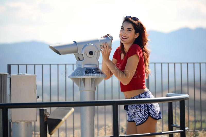 Belle fille regardant le paysage par la pièce de monnaie binoculaire photographie stock libre de droits