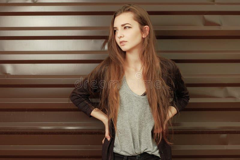 Belle fille regardant loin se penchante de retour contre la barrière en métal La jeune fille de hippie s'est habillée dans appréc image libre de droits