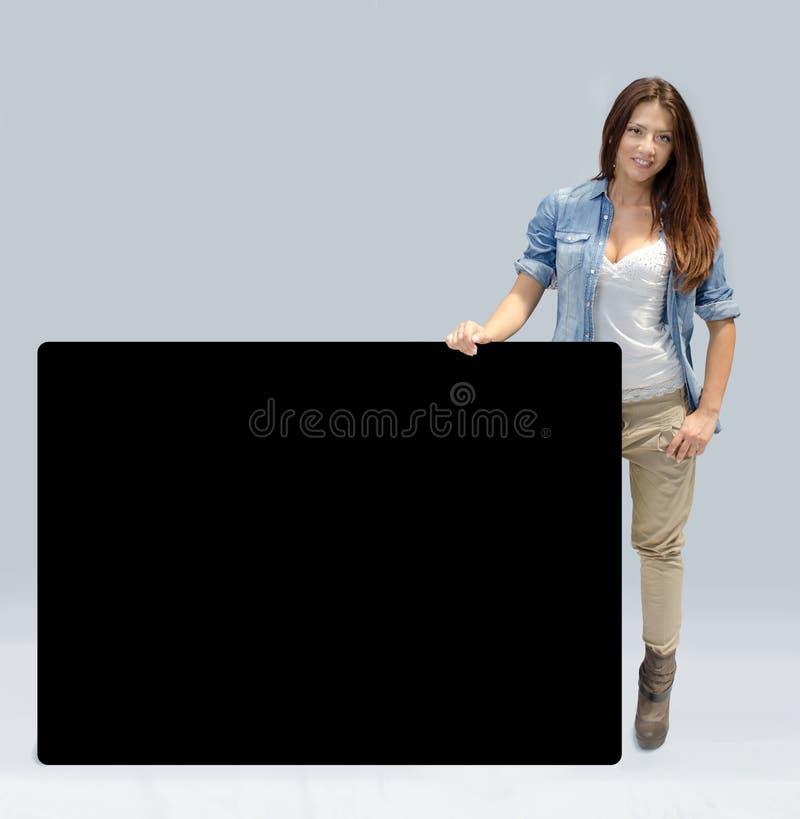 Belle fille retenant le grand panneau noir photos stock
