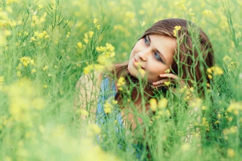 Belle fille romantique sur le champ de fleurs de colza en profitant de la jeune femme élégante de nature à pied le concept assez f