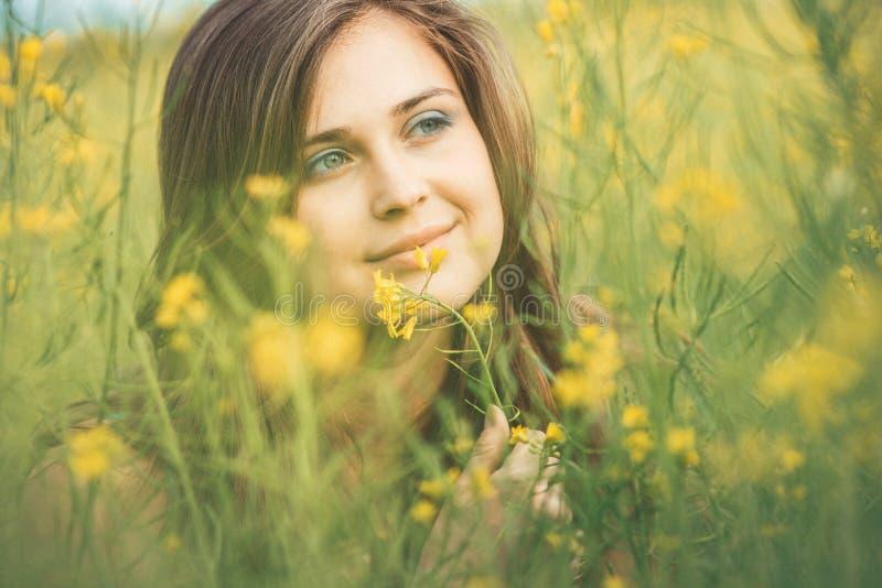 Belle fille romantique sur le champ de fleurs de colza en profitant de la jeune femme élégante de nature à pied le concept assez f photo libre de droits