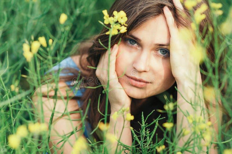 Belle fille romantique sur le champ de fleurs de colza en profitant de la jeune femme élégante de nature à pied le concept assez f images stock