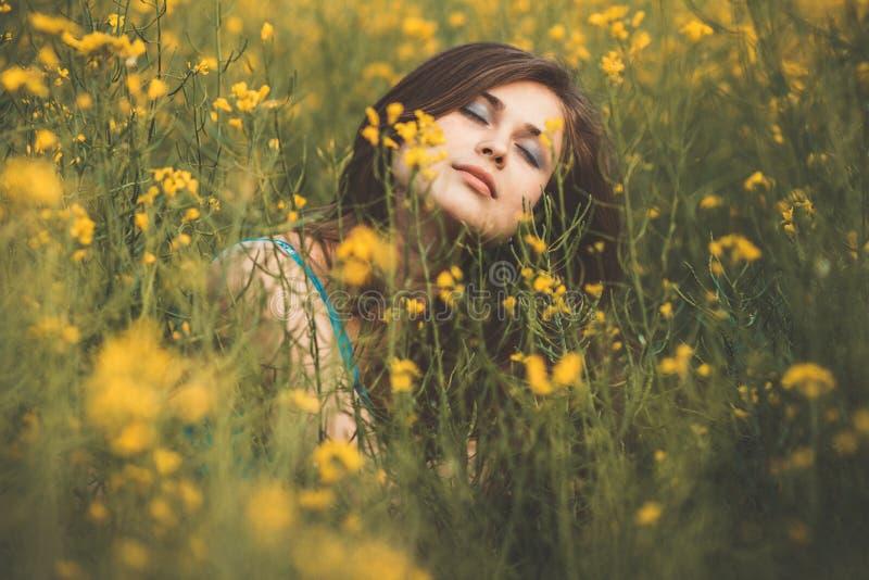 Belle fille romantique sur le champ de fleurs de colza en profitant de la jeune femme élégante de nature à pied le concept femelle