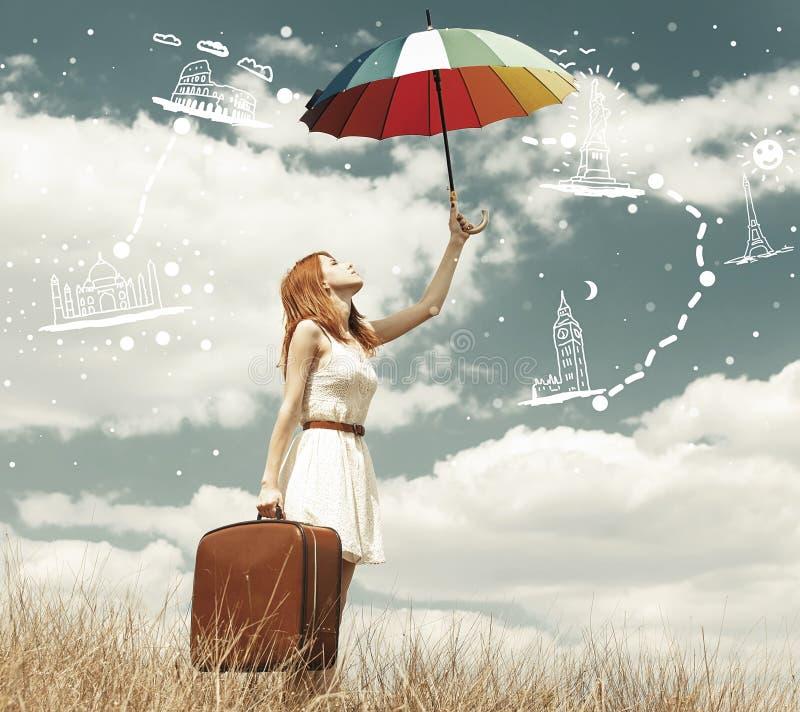 Belle fille rousse avec le parapluie et la valise à extérieur photo stock