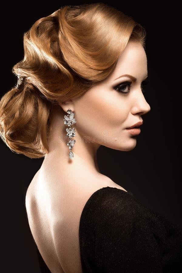 Belle fille rousse dans une robe noire avec une coupe de cheveux douce de soirée sous forme de vagues et de maquillage lumineux V photographie stock libre de droits